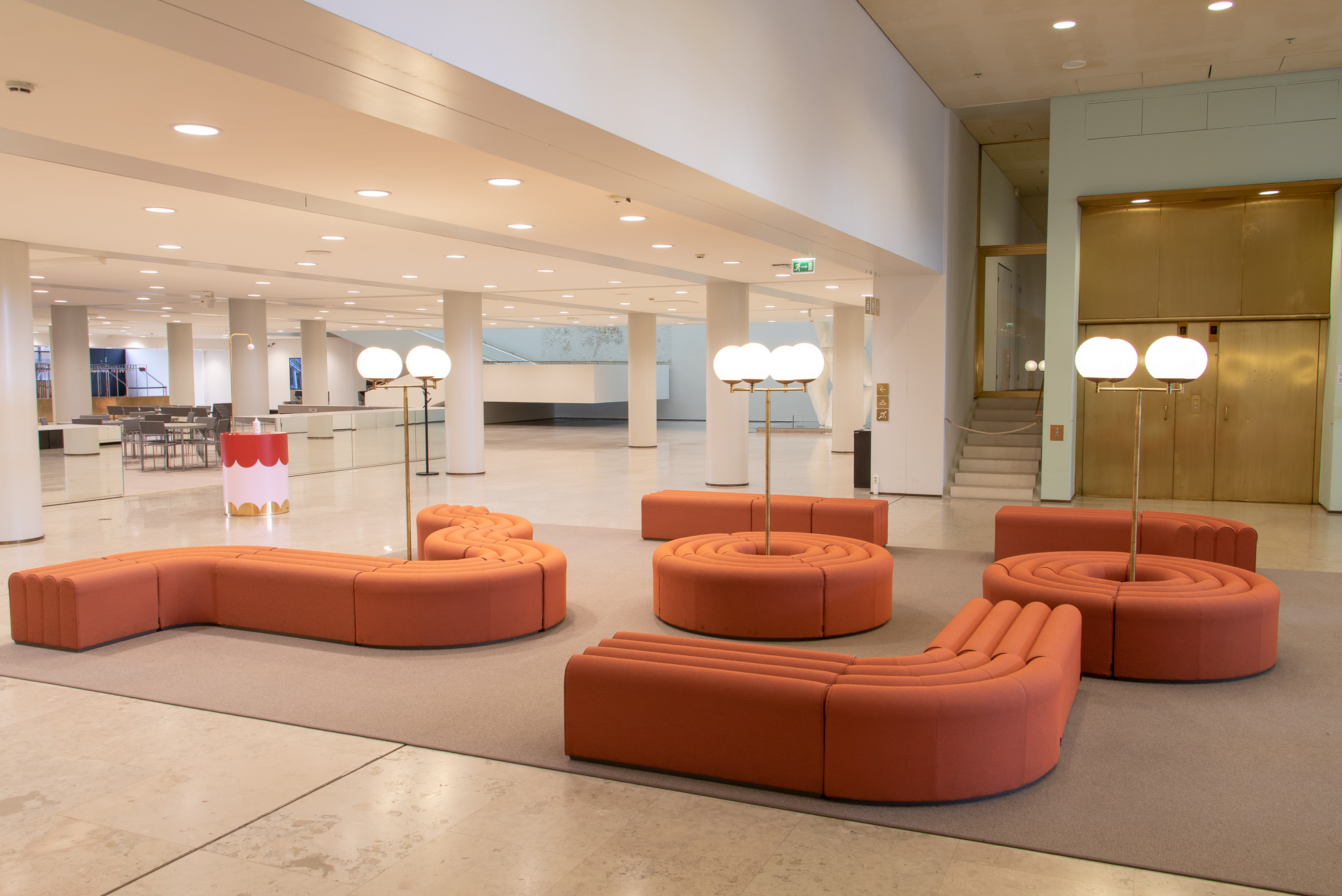 A reddish sofa and round-shaped lamps in the lobby.