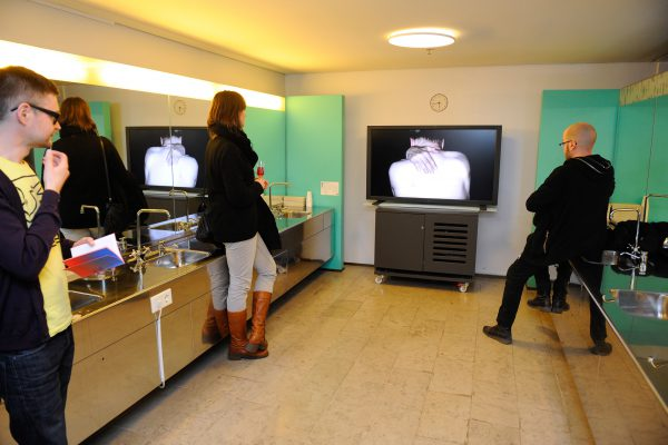 Video art is displayed in City Hall's toilets. People are watching a video in the middle of mirrors, and one of them is sitting on a sink. Another is holding a glass of wine.