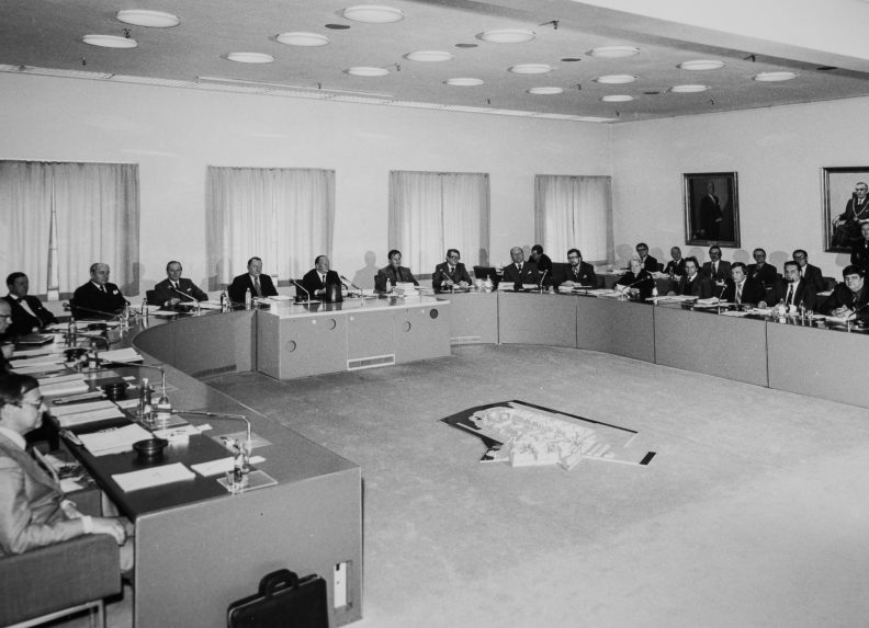 The Board is gathered around a crescent table. The presiding officers are in the centre. A scale model of the harbour is on the floor.