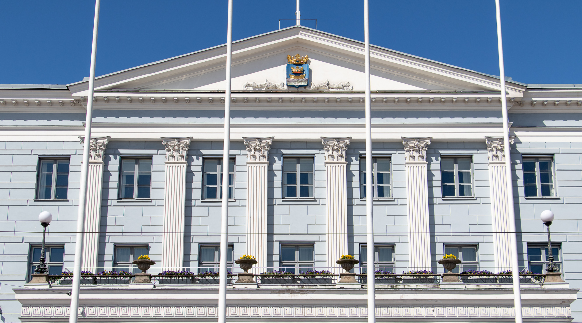 City Hall has several windows facing the Market Square. There are four flagpoles in front of the mayor's balcony. The Coat of Arms of Helsinki is above the balcony.