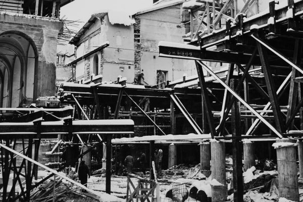 Dozens of steel and concrete beams have been installed to support the future structures. Workers in a snowy outdoor construction site. Old buildings torn open.