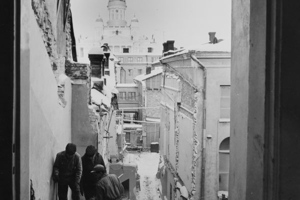 Three construction workers working at the top of an old staircase. The view opens up past the block and you can see the Helsinki Cathedral in the background.