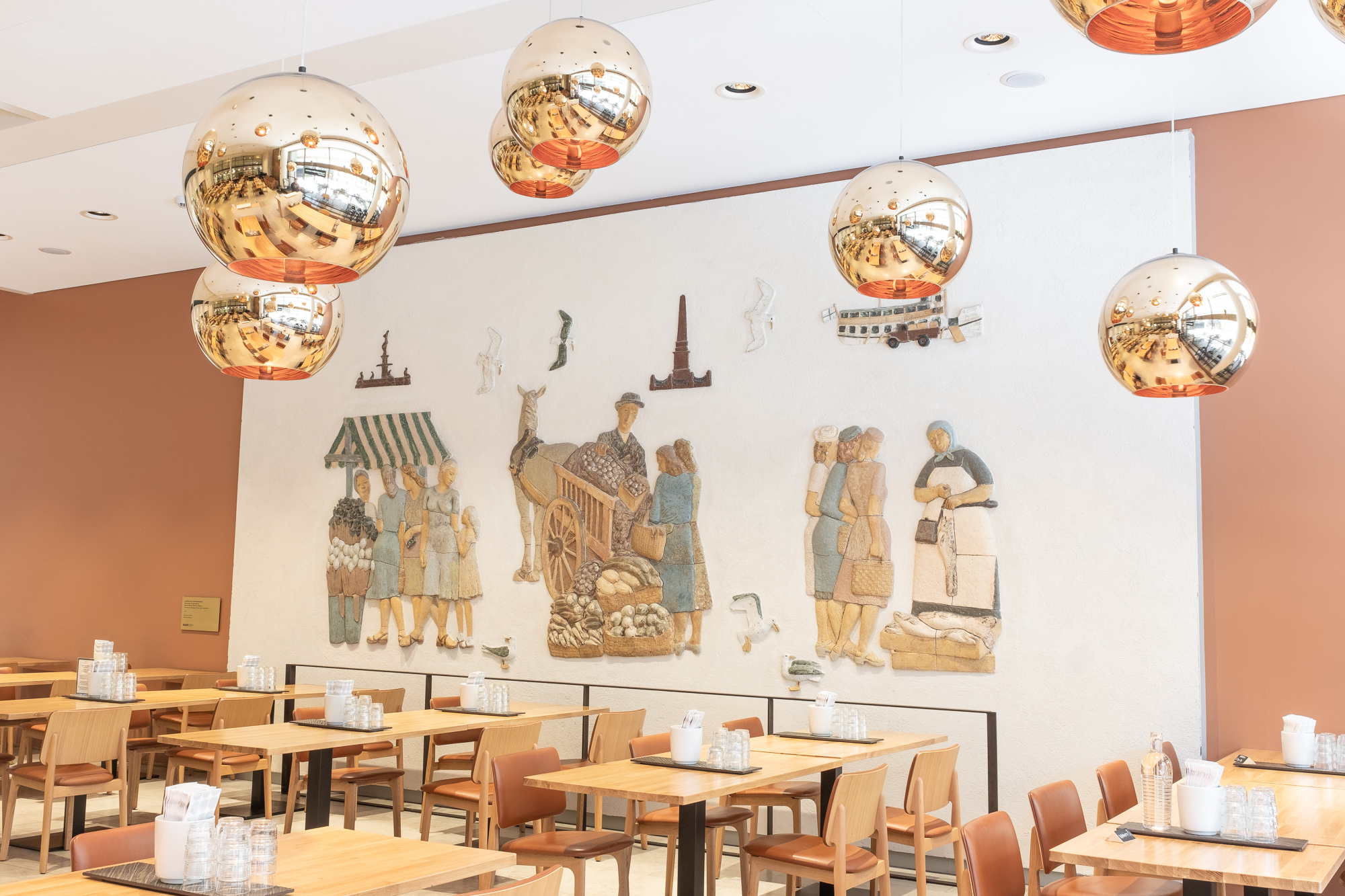 Characteristic round-shaped lamps are in the restaurant, which reflect the restaurant's interior. A relief by Schilkin, depicting the Market Square and its seagulls, is on the wall.