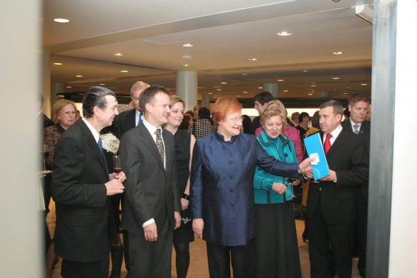 President Tarja Halonen is examining the exhibition surrounded by diplomatic officials and other opening quests.