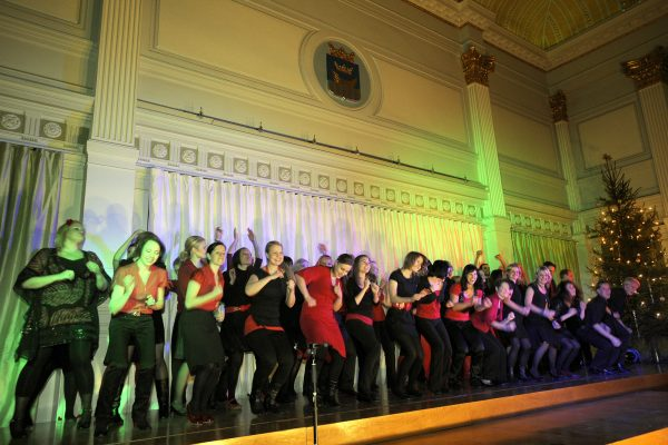 The choir, dressed festively, is dancing wildly on the stage of the banquet hall.