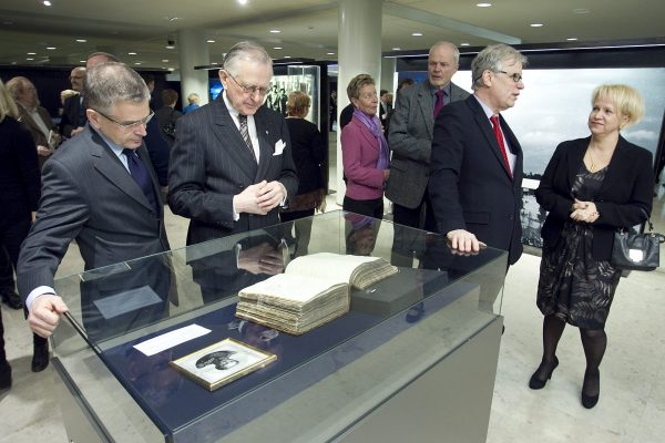 A display case containing a book and print image is in the foreground. Jussi Pajunen and Matti Klinge are standing behind the display case. Other opening guests in the background.