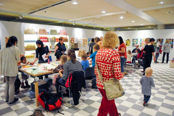The exhibition space resembles an old shop. There are ad posters and food tins on the walls. The children are engaged in crafts with their parents at a long table.