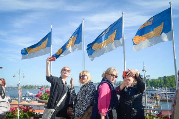 Four women taking selfies on the mayor's balcony. The sun is shining. Flags with the Helsinki Coat of Arms are waving in the wind.