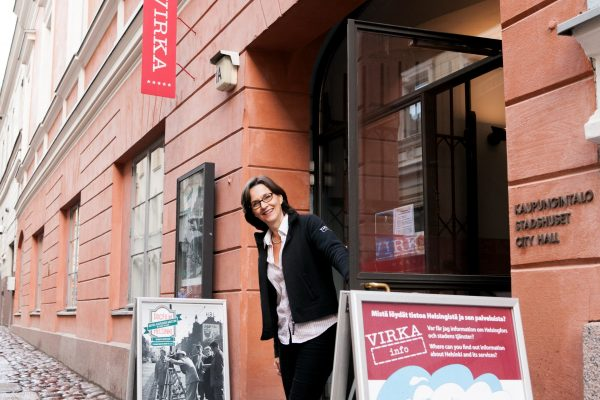 """Woman standing smiling at the Sofiankatu door of the City Hall. Poster stands can be seen on both sides of the door. A red sign that reads """"Virka"""" in white is above the doorway."""