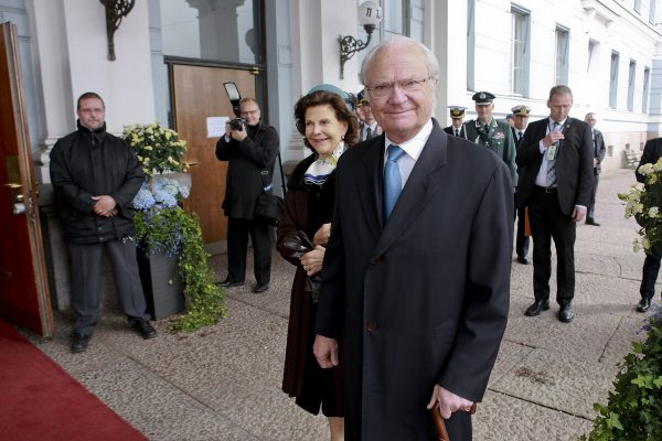 King Carl XVI Gustaf of Sweden standing in front of the City Hall entrance, looking amiably at the camera with Queen Silvia behind him. A photographer and security staff are at the door.