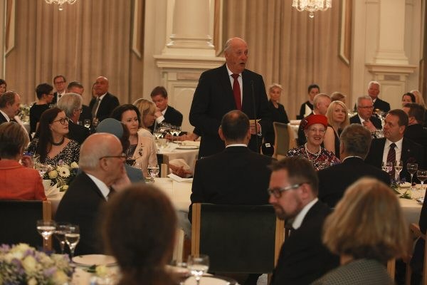 The banquet hall is filled with invited guests. King Harald V is speaking standing up in the middle of the hall. Queen Margrethe II of Denmark is sitting to his right, with Jan Vapaavuori next to her.