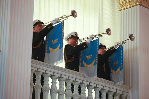 Three trumpet players in the gallery standing and playing. The trumpets feature the Coat of Arms of Helsinki.