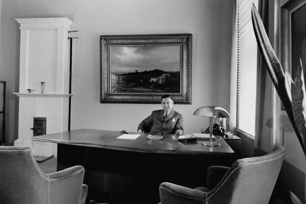 The mayor is sat behind a large desk. A landscape painting is behind him on the wall, and a masonry heater stands in the background.
