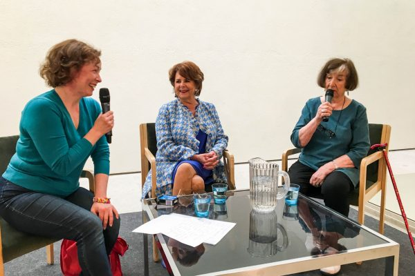 Joanna Weckman, Pirkko Mannola and Heidi Krohn sitting at a table set up on stage, talking and laughing together.