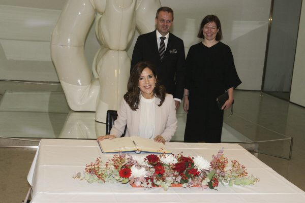 The Crown Princess Mary sitting at a table in the lobby. A guest book is on the table. Jan Vapaavuori and Anni Sinnemäki are standing behind her.