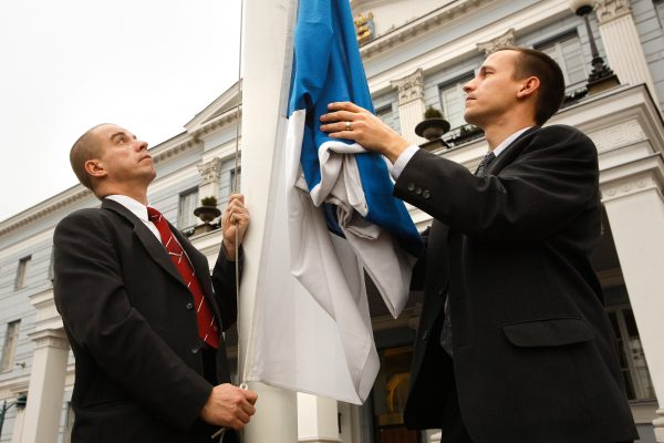 The Finnish flag being hoisted up with joint effort.