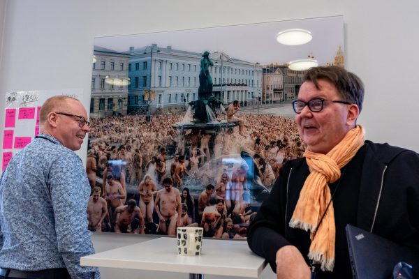 Men are laughing merrily. A large photo of the statue Havis Amanda, surrounded by hundreds of naked people, is hung on the wall. The powder blue facade of the City Hall block is in the background of the photo.