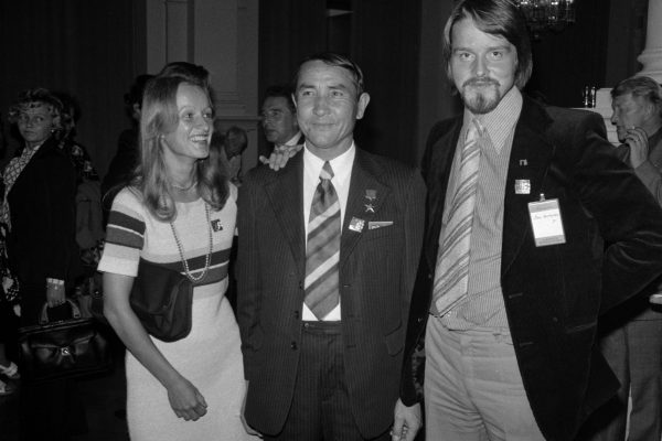 A woman and two men standing side by side smiling.