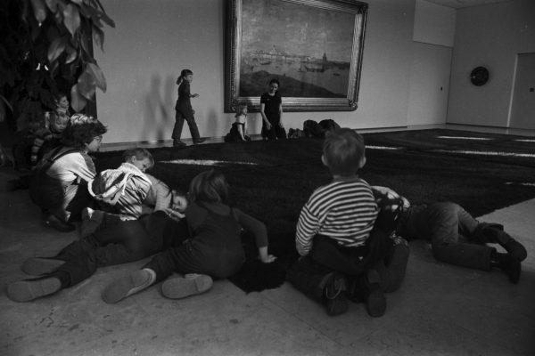 """Children lying on a decorative """"ryijy"""" rug on the floor of the Mayor's reception foyer. A painting of Helsinki by Oscar Kleineh can be seen on the wall."""