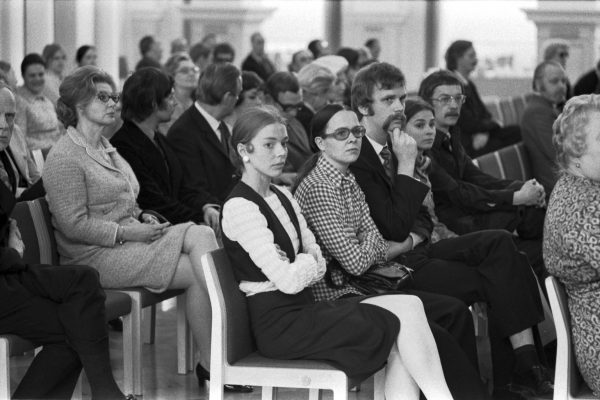 A group of solemn people sitting on rows of benches in the banquet hall.