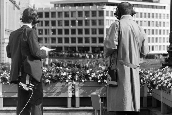 Two journalists standing on the balcony and looking towards Enso Gutzeit's head office with headphones on and dictation machines hanging from their shoulders.