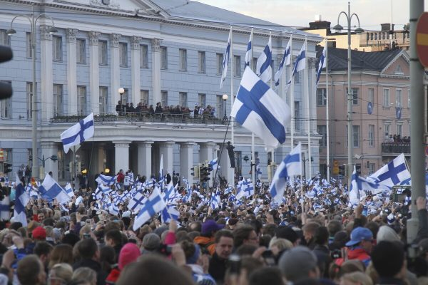 A large group of people waving Finnish flags congregated in front of the City Hall. There are also a lot of people on the City Hall balcony.